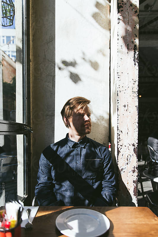 Man Sitting In The Shadows Of A Cafe by Laura Austin for Stocksy United