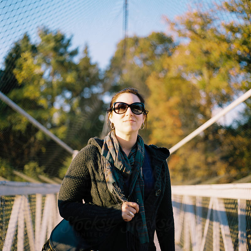 Woman on a suspension bridge at sunset in autumn by Joey Pasco for Stocksy United