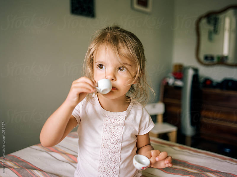 little girl playing with tea set by Maria Manco for Stocksy United