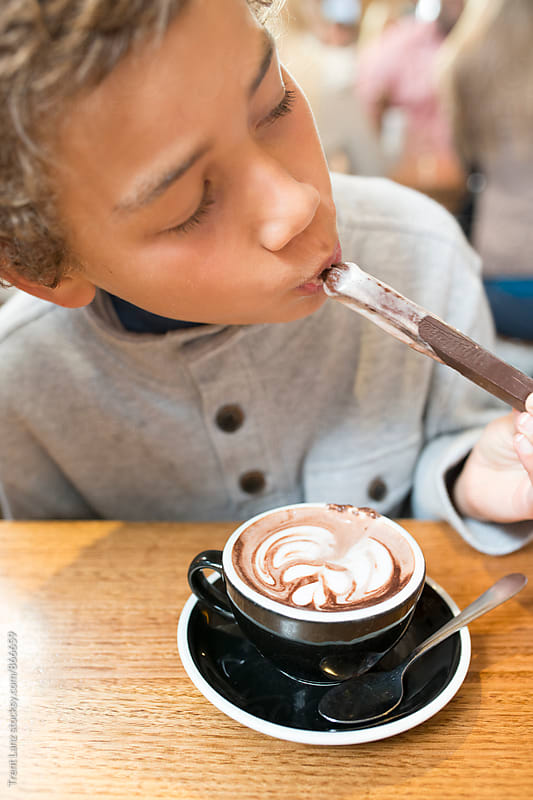 Boy eating chocolate stick and drinking hot cocoa by Trent Lanz for Stocksy United