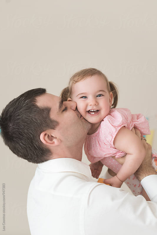 Father lifting up his daugher in the air and kissing her cheek by Lea Csontos for Stocksy United