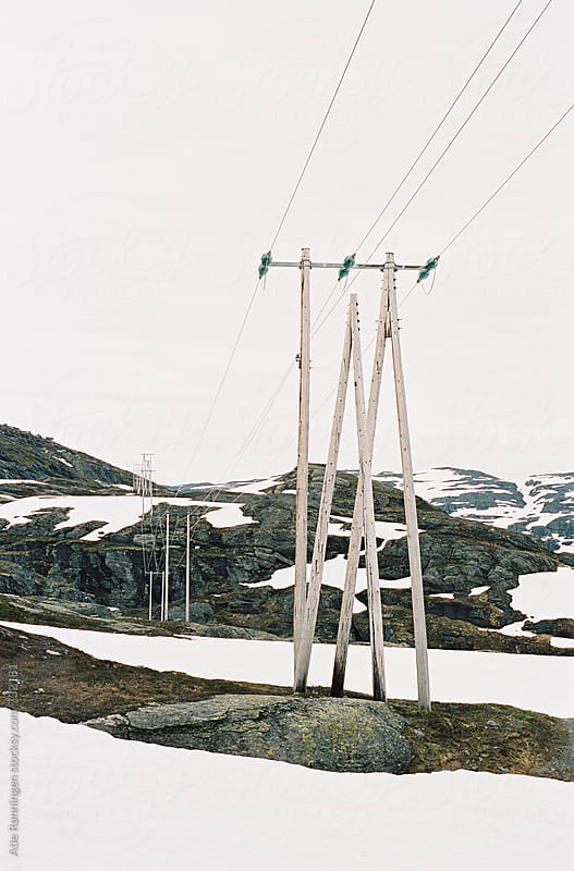 Power cords trough the Norwegian mountain landscape in snowy July by Atle Rønningen for Stocksy United
