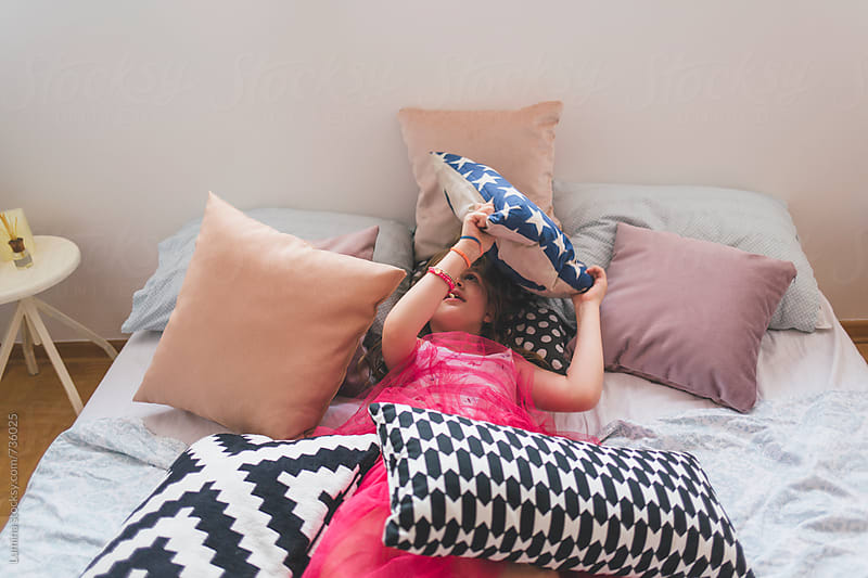 Girl Playing With Pillows in the Bedroom by Lumina for Stocksy United