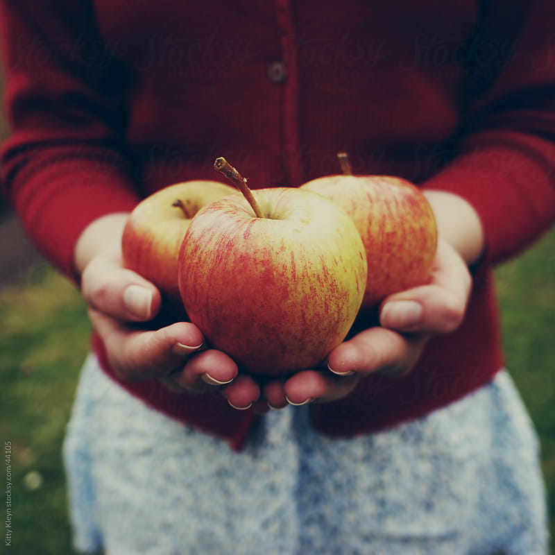 Holding apples by Kitty Gallannaugh for Stocksy United