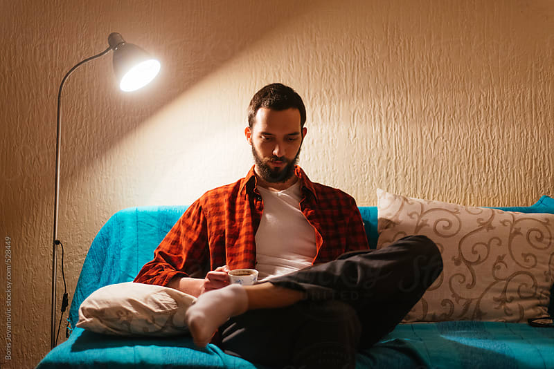 Man drinking coffee and reading a magazine by Boris Jovanovic for Stocksy United