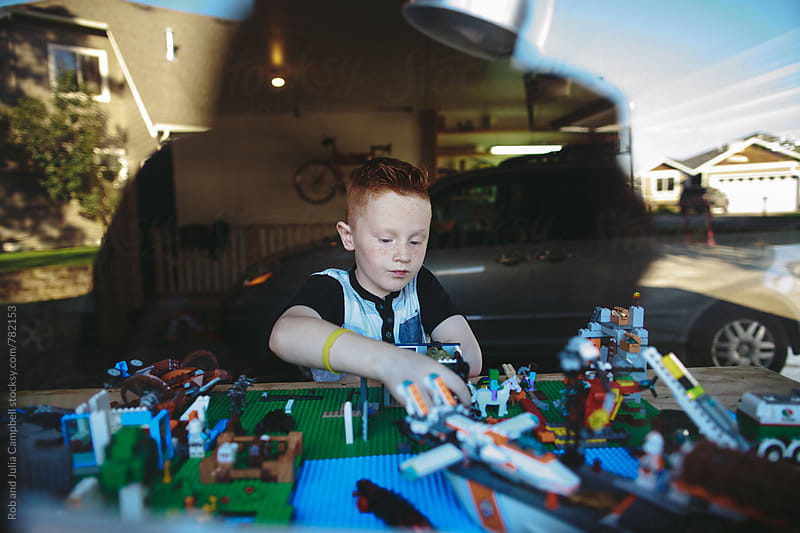 Serious, concentrating boy working on building blocks by Rob and Julia Campbell for Stocksy United