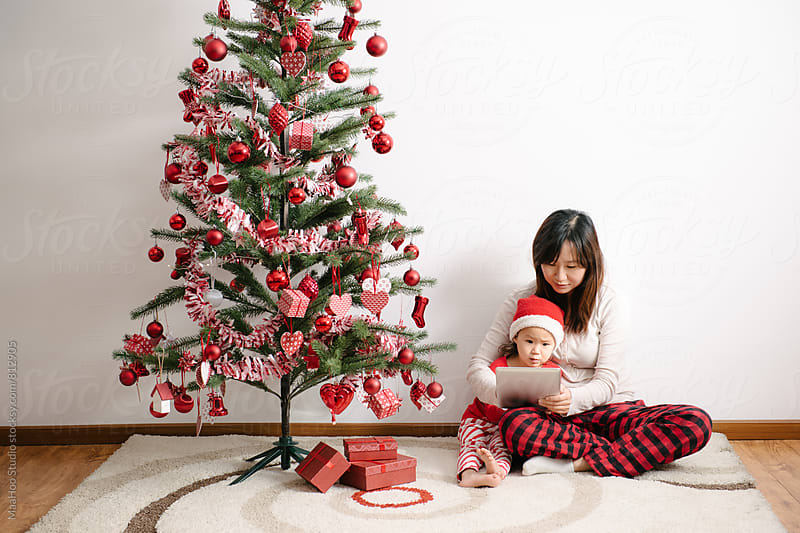 Toddler girl and her mother using digital PC by christmas tree by Maa Hoo for Stocksy United