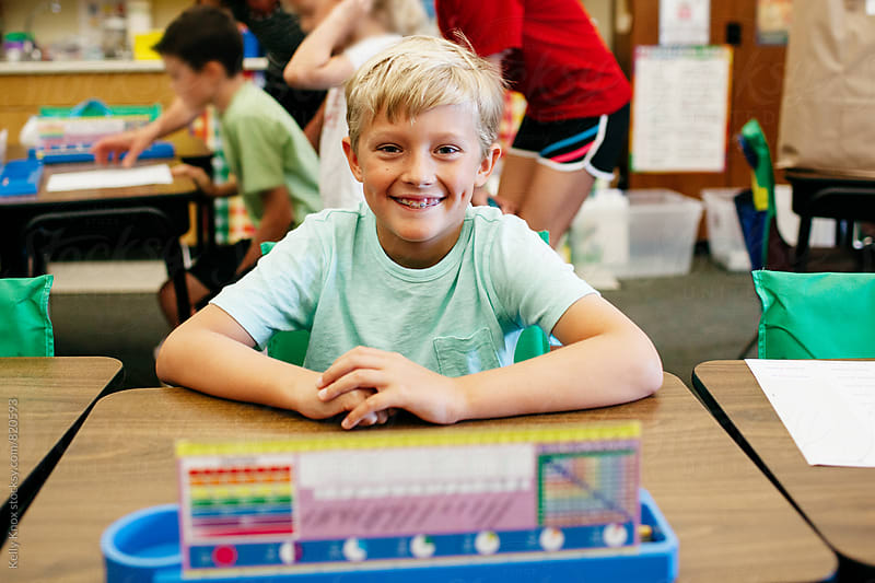 smiling student sitting at his desk by Kelly Knox for Stocksy United