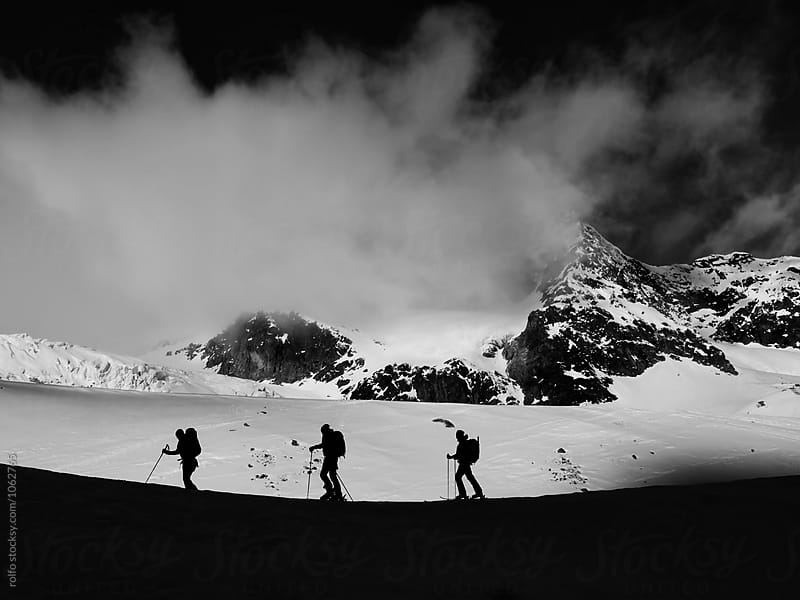 Three alpinists walking against of foggy mountain peak by rolfo for Stocksy United