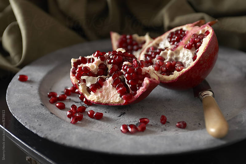 Pomegranate cut and seeds pulled out on pewter plate by Sherry Heck for Stocksy United