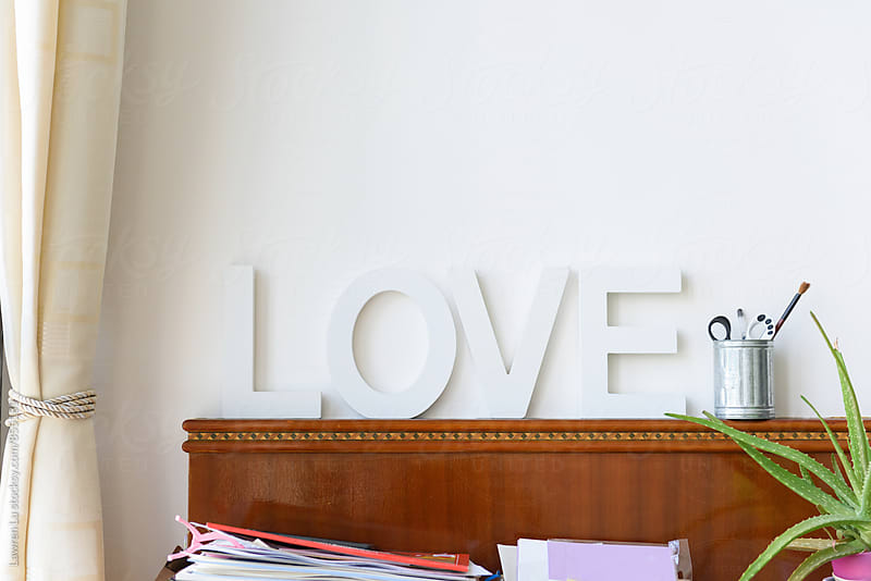 White Love word stand aginst pure wall  in home by Lawren Lu for Stocksy United