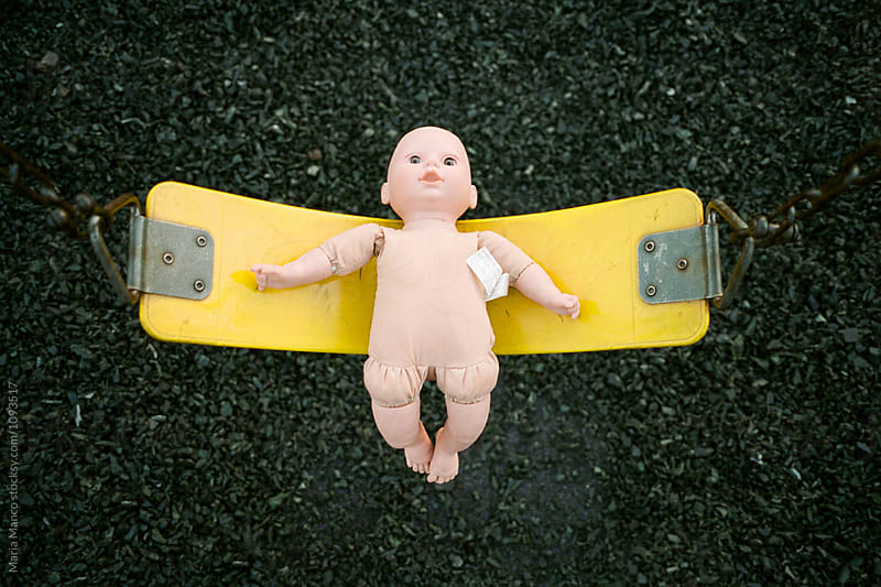 creepy doll on swing by Maria Manco for Stocksy United