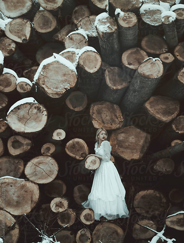 Girl standing on a woodpile by Jovana Rikalo for Stocksy United