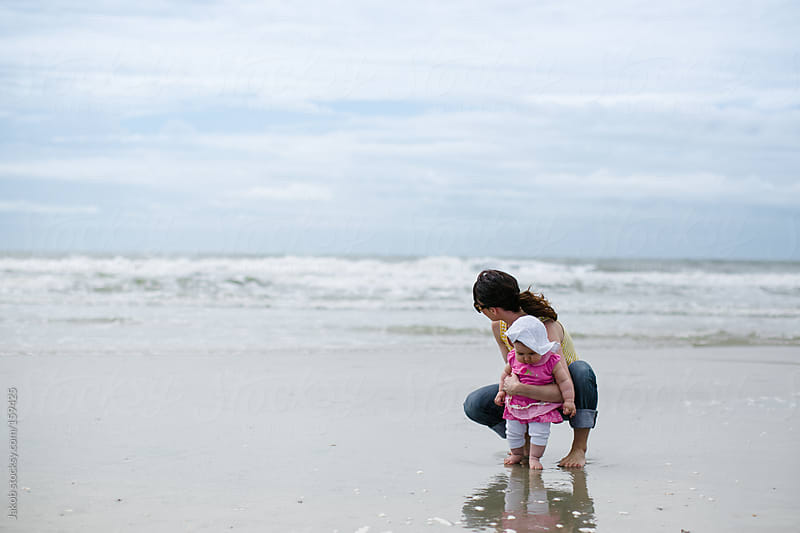 A mother and daughter playing on a beach by Jakob for Stocksy United
