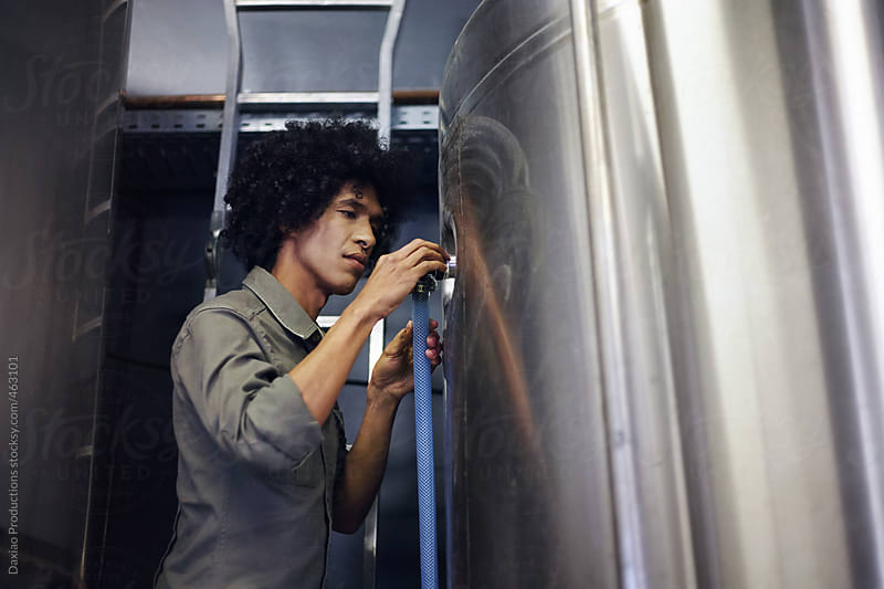 Beer brewmaster doing maintenance in the brewery by Daxiao Productions for Stocksy United