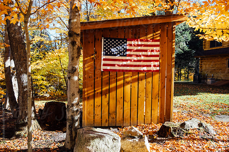 Flag on wooden hut by Léa Jones for Stocksy United