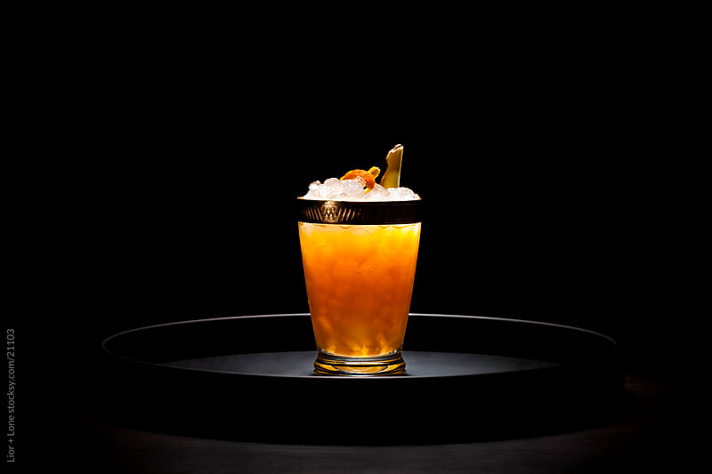 Large orange cocktail on round tray by Lior + Lone for Stocksy United
