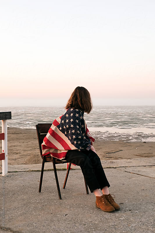 Girl on chair in American flag looking back at sky by Danil Nevsky for Stocksy United