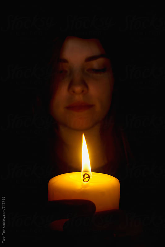 young woman's face illuminated by candle by Tana Teel for Stocksy United