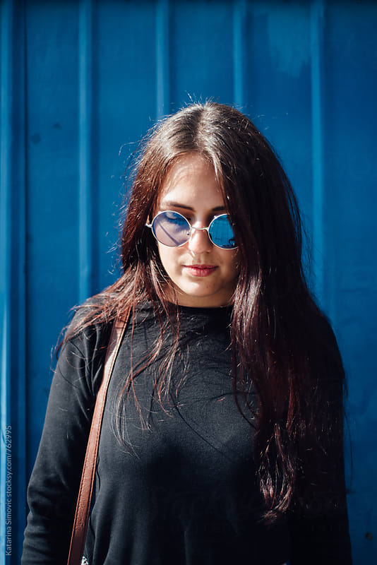 Portrait of beautiful woman with blue sunglasses by Katarina Simovic for Stocksy United