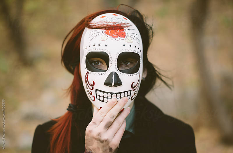 young woman wearing a Mexican sugar skull mask . by Alexey Kuzma for Stocksy United