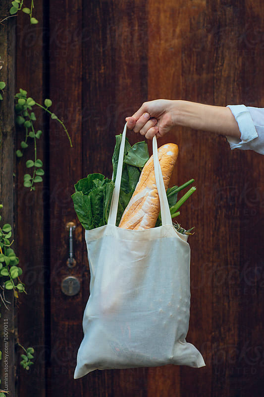Hand of a Woman Holding a Tote Bag with Bread and Vegetables by Lumina for Stocksy United