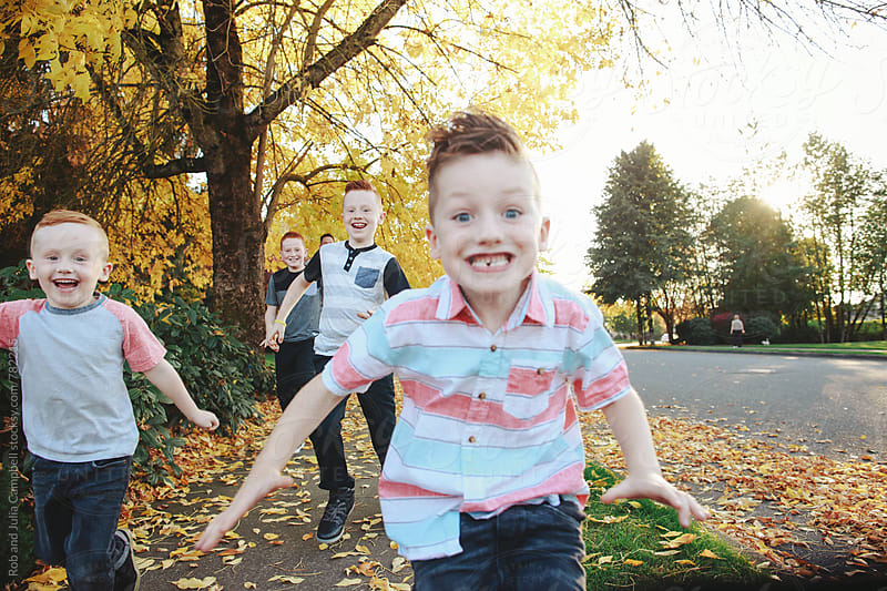 Young brothers having fun together outside - running toward camera by Rob and Julia Campbell for Stocksy United