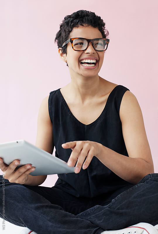 Young woman with glasses smiling and using a tablet pc. by W2 Photography for Stocksy United