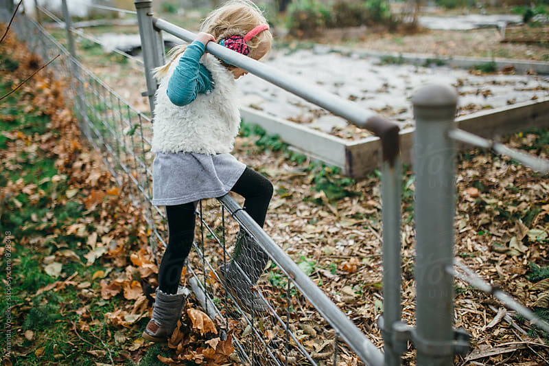 Little Girl Climbs through a Garden Gate by Amanda Voelker for Stocksy United