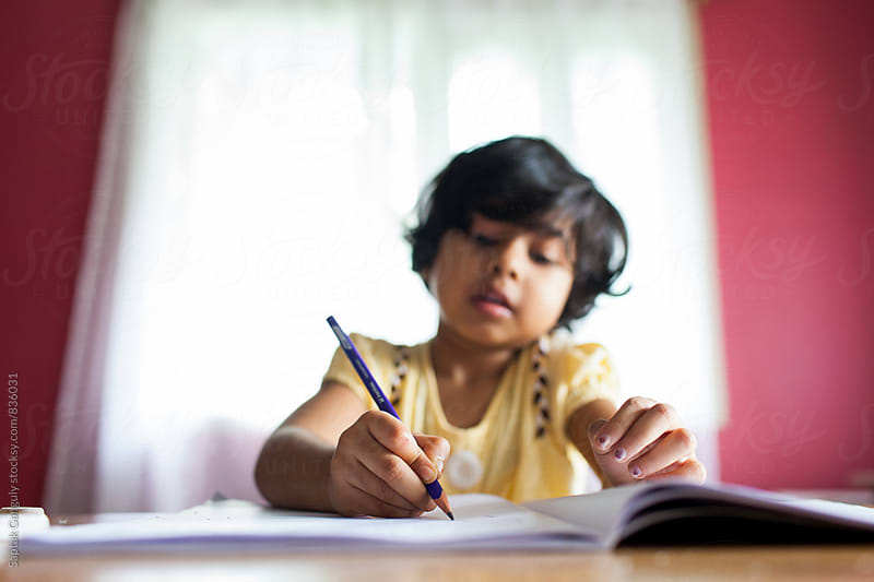 A little girl writes in a notebook by Saptak Ganguly for Stocksy United