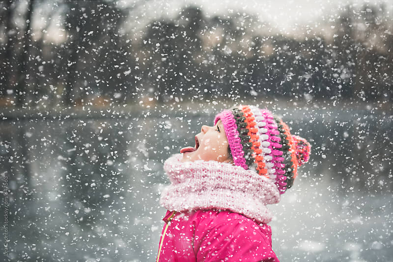 Cute little girl sticking her tongue out and catching snowflakes by Lea Csontos for Stocksy United