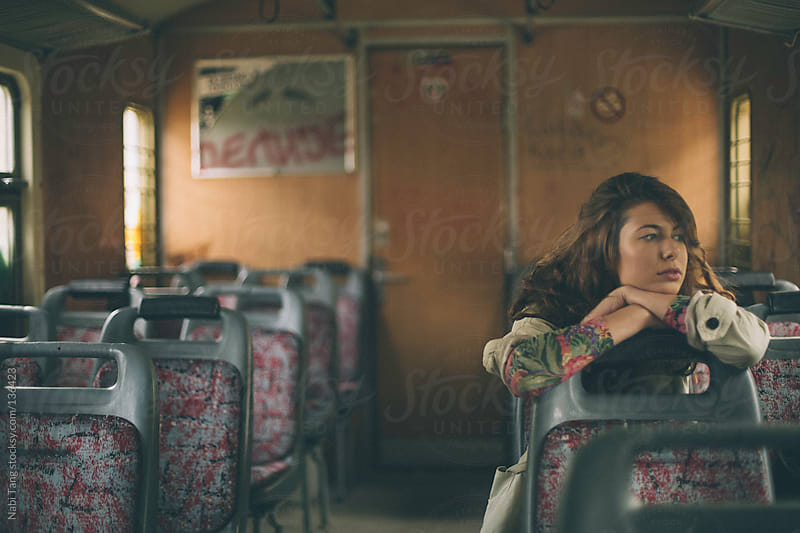 Beautiful young woman sitting alone in the train by Nabi Tang for Stocksy United