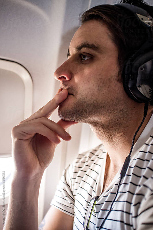 Man with headphones on a plane next to window by J Danielle Wehunt for Stocksy United