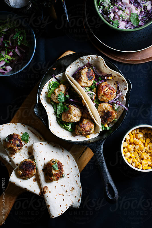 Meatball tacos and side dishes of salad and corn and slaw on a dark background. by Darren Muir for Stocksy United