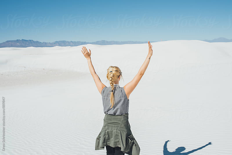 Young woman puts arms up in the air in desert  by Drew Schrimsher for Stocksy United