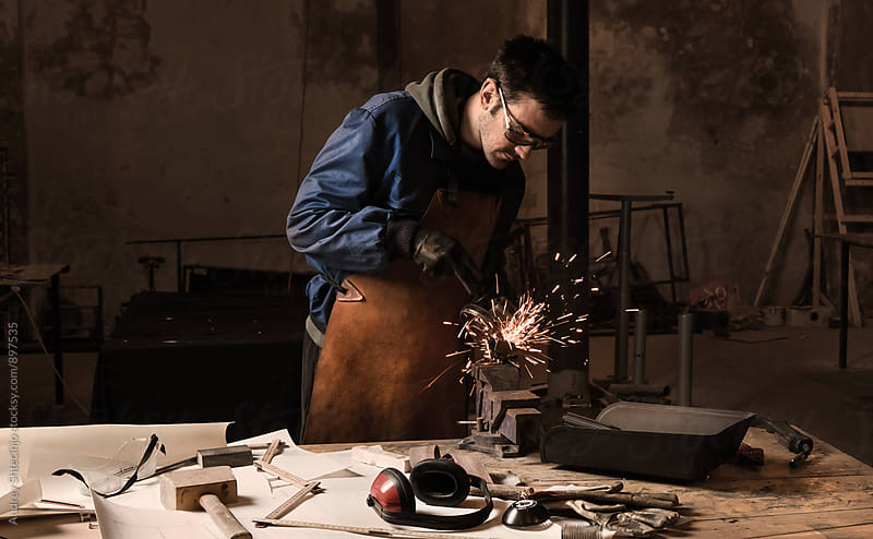 Young man working in his small workshop with grinder machine. by Audrey Shtecinjo for Stocksy United