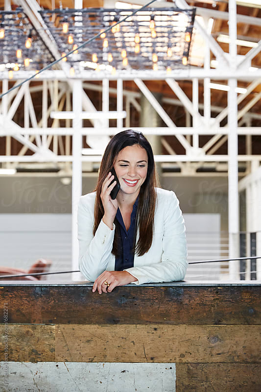 Portrait of millennial Hispanic businesswoman on phone by Trinette Reed for Stocksy United