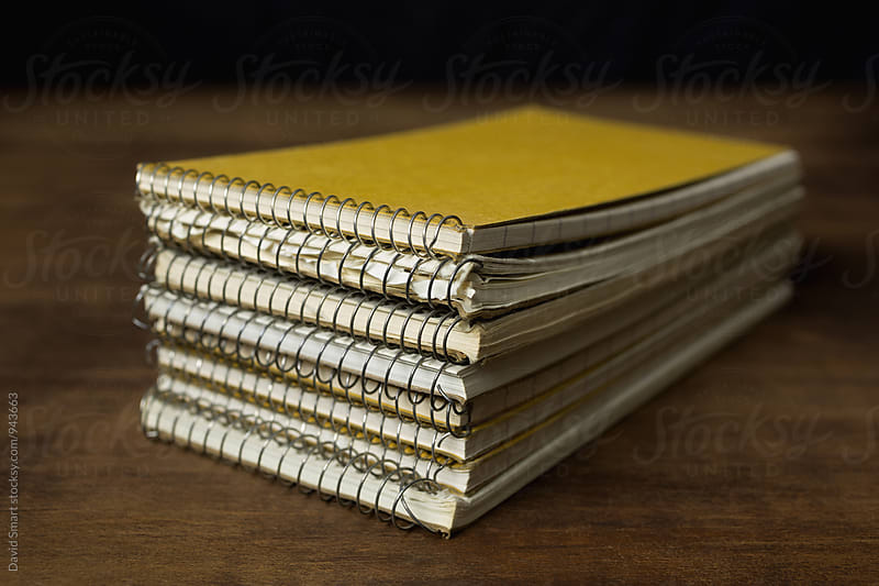Reporter's notebooks stacked on a wooden table. by David Smart for Stocksy United