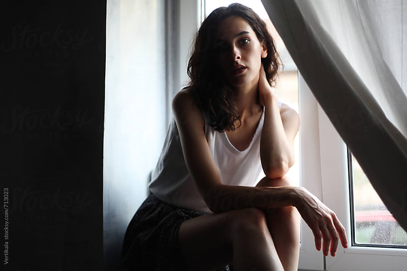 Beautiful woman sitting near a window on a natural light  by VeaVea for Stocksy United