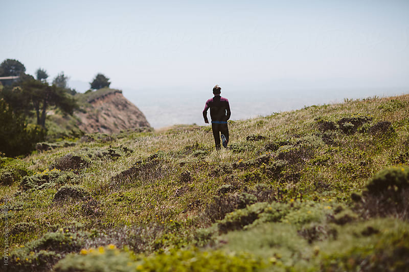 Young man runs along California bluff by HOWL for Stocksy United
