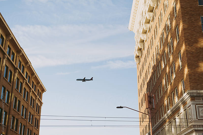 Airplane in City by Caleb Thal for Stocksy United
