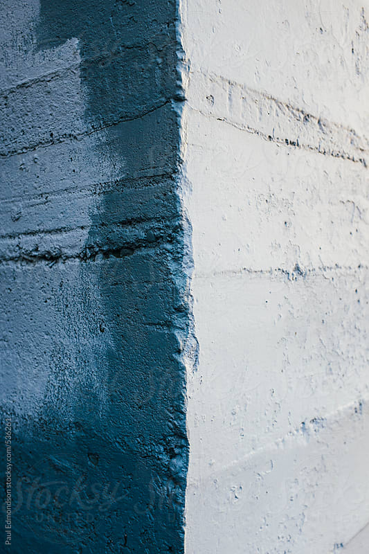 Corner of painted blue wall, covering graffiti markings, close up by Paul Edmondson for Stocksy United