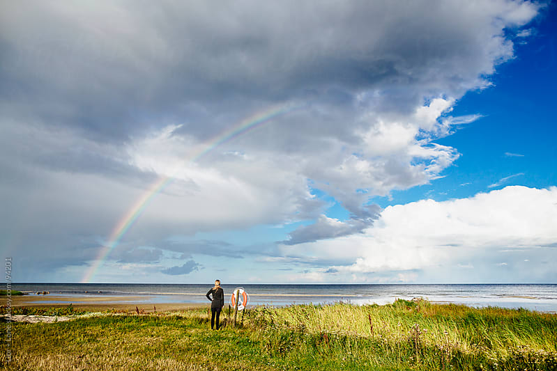 Woman standing by the beach watching rainbow by Lior + Lone for Stocksy United