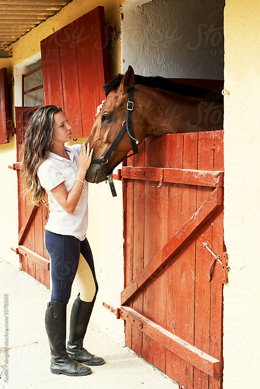 brunette rider stroking her brown horse by Guille Faingold for Stocksy United