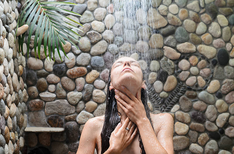 Beautiful young woman with long hair taking a shower outdoors by Alice Nerr for Stocksy United