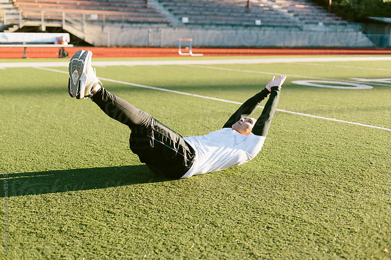 Athletic Man Reaching For Toes During Abdominal Crunch Workout On Turf Field by Luke Mattson for Stocksy United