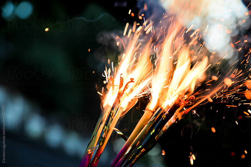Handfull of sparklers going off on the 4th of July by Carolyn Lagattuta for Stocksy United