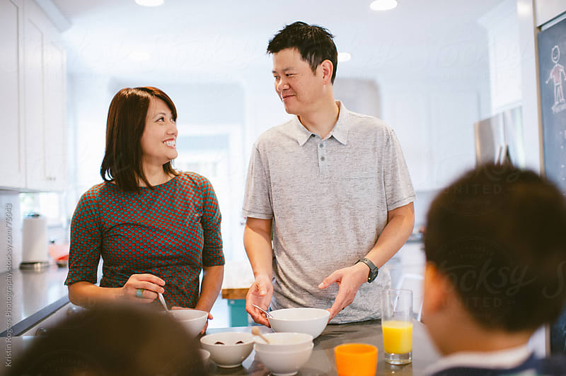Husband and Wife Smile in kitchen as they serve breakfast by Kristin Rogers Photography for Stocksy United