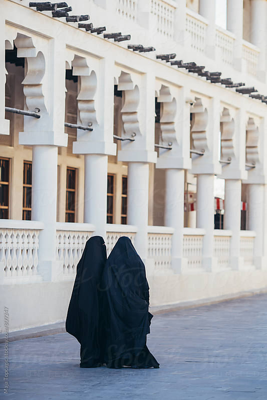 Two women in abayas walking in Doha by Maja Topcagic for Stocksy United