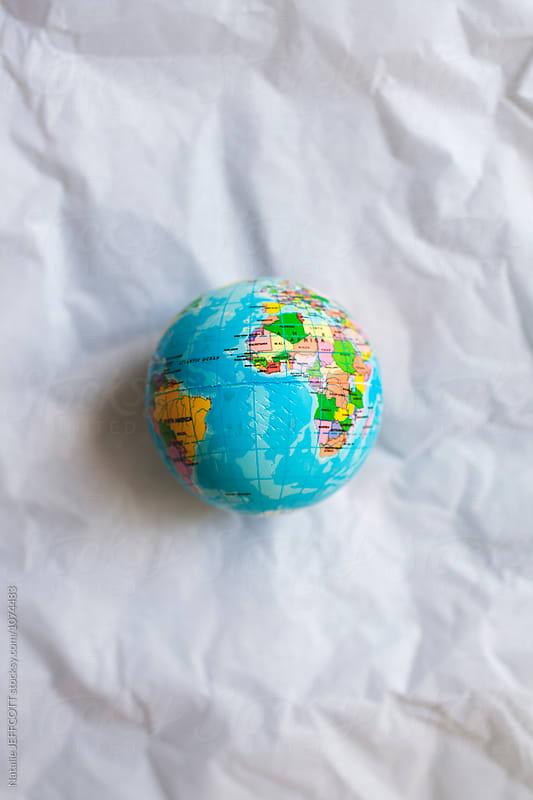 A small world globe on white tissue paper by Natalie JEFFCOTT for Stocksy United